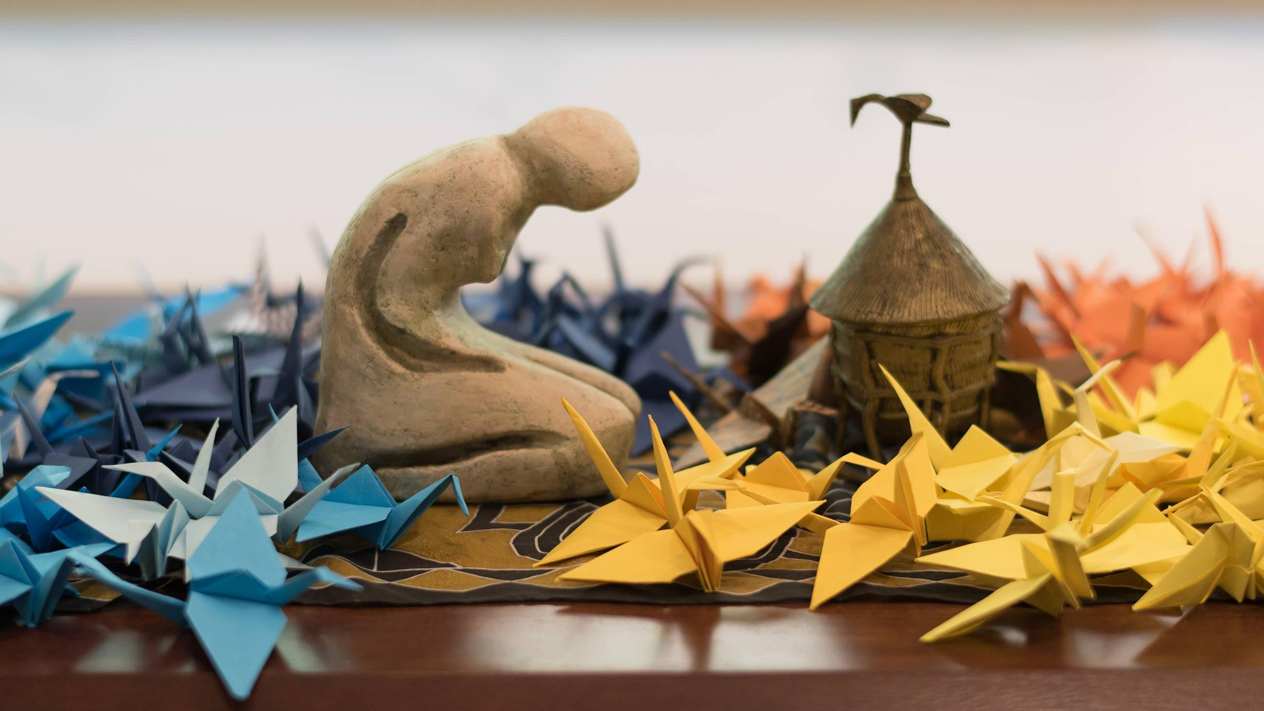 Small statue kneeling among multi-colored paper cranes