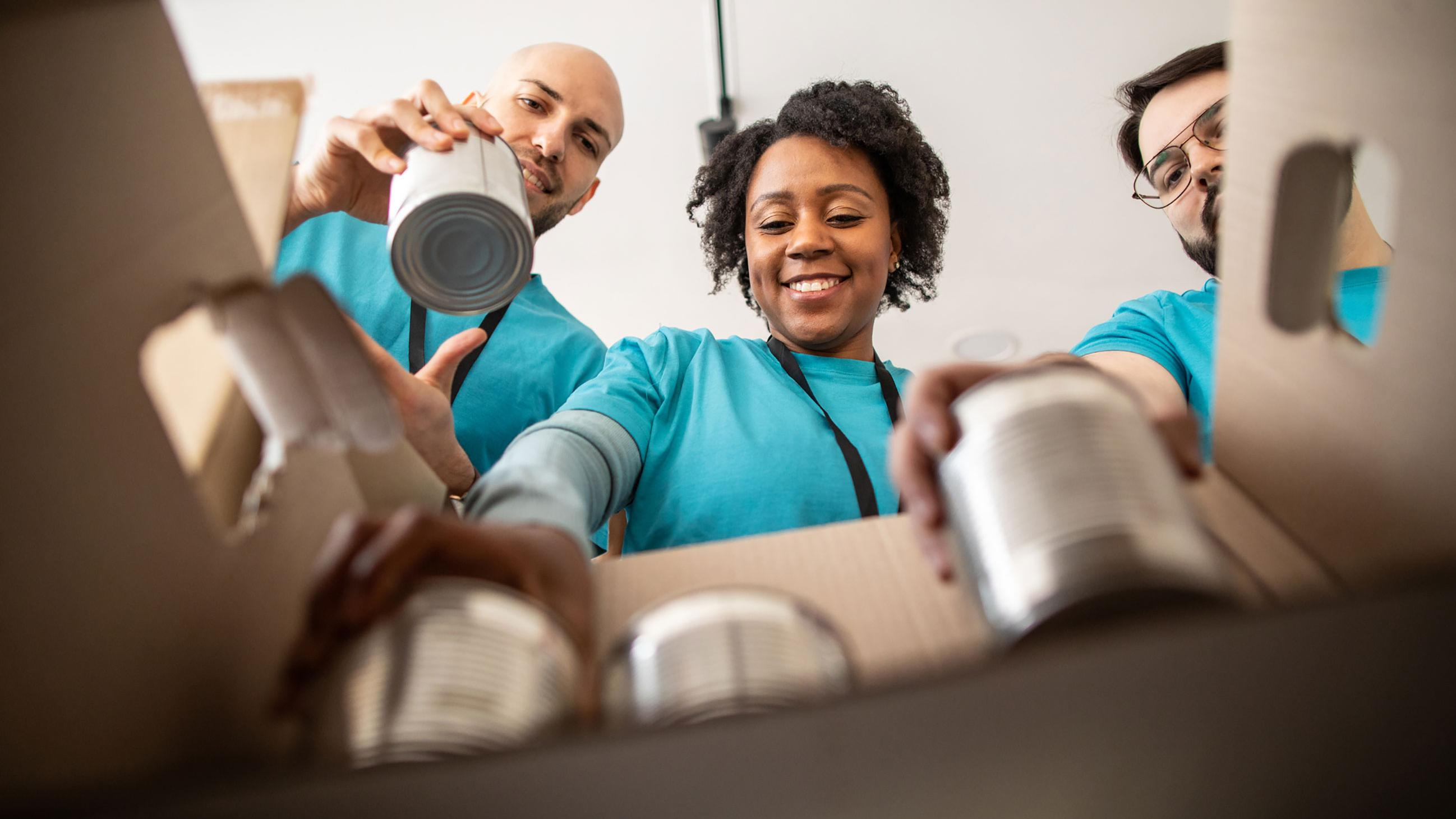 Three people happily loading cans into a box
