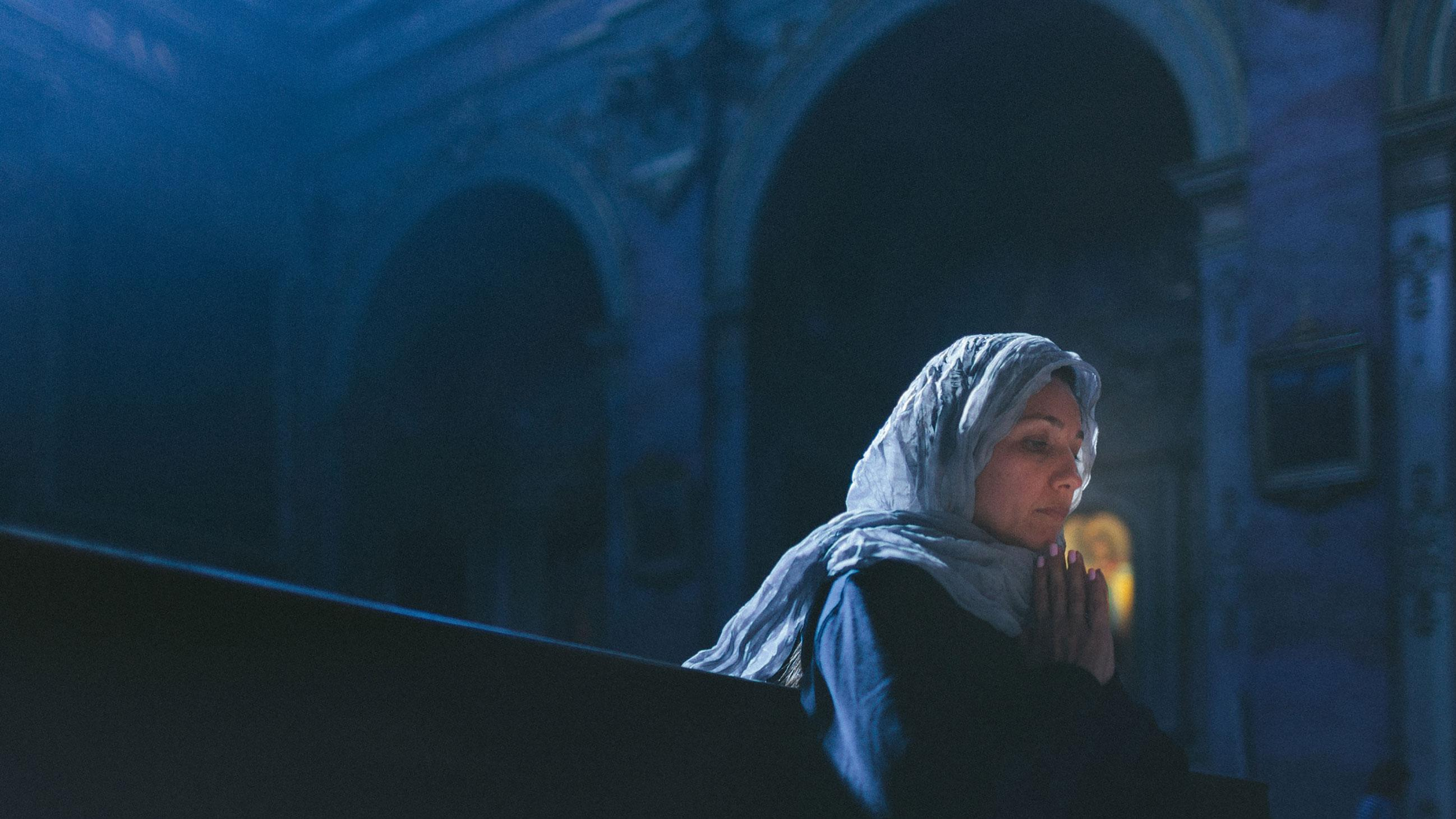Woman with head cover alone in religious setting