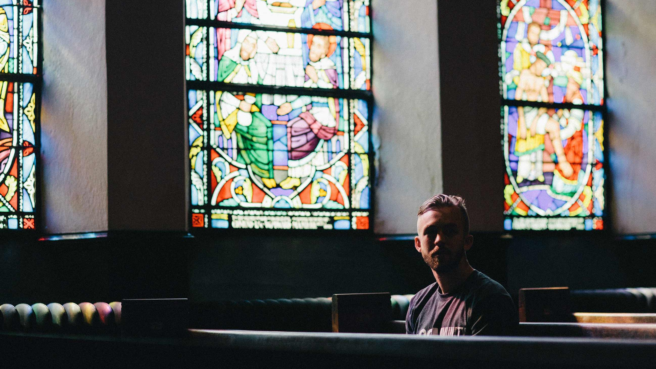 Man sitting in pews beneath large stained glass windows