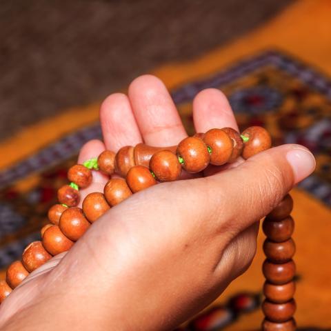 Hand holding religious beads